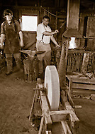 Old Bethpage, New York, U.S. 29th September 2013. Christopher Van Wickler, of Massapequa, is the Master Blacksmith, and ROSS JONES, of Bellmore, is his apprentice, at The Long Island Fair. A yearly event since 1842, the county fair now is held at a reconstructed fairground at Old Bethpage Village Restoration.