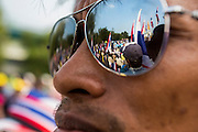 "09 DECEMBER 2013 - BANGKOK, THAILAND: Other anti-government protestors are reflected in the sunglasses of a protestor at Government House in Bangkok. Thai Prime Minister Yingluck Shinawatra announced she would dissolve the lower house of the Parliament and call new elections in the face of ongoing anti-government protests in Bangkok. Hundreds of thousands of people flocked to Government House, the office of the Prime Minister, Monday to celebrate the collapse of the government after Yingluck made her announcement. Former Deputy Prime Minister Suthep Thaugsuban, the organizer of the protests, said the protests would continue until the ""Thaksin influence is uprooted from Thailand."" There were no reports of violence in the protests Monday.      PHOTO BY JACK KURTZ"