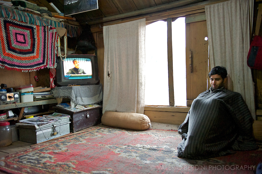Young man keep warm in a traditional kashmiri woollen dress sits in the living room of a comfortable houseboat docked on the Jelhum river in Srinagar. Kashmir. India
