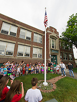Richard Conrod and his 7-8th grade students lead the school in a Memorial Day Service on the front lawn at Holy Trinity Catholic School Friday morning.  (Karen Bobotas/for the Laconia Daily Sun)