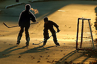 Gloucester: .Michael Russo, left, and Coltyn Rivas, both 10, play street hockey on Riverside Avenue at sunset Tuesday afternoon..Photo by Mike Dean/Gloucester Daily Times. Tuesday, December 14, 2004