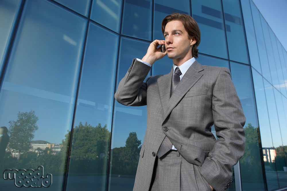 Business man using mobile phone outside office building
