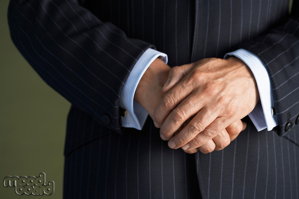 Middle-aged businessman in full suit hands clasped mid section close-up