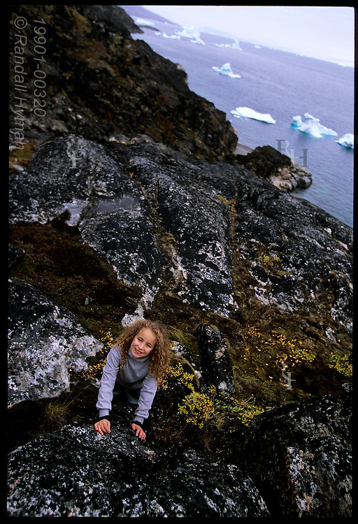 Little girl poses amid granite rock outcrop overlooking icebergs and fjord at the famous Qilakitsoq mummy site; Greenland