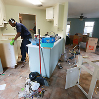 Hugh Foster of Service Master continues to remove the kitchen cabinets from a Willow Creek home at was flooded during last weeks flooding.
