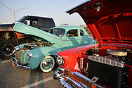 Bellmore, New York, USA. August 24, 2018. Visitors at left finish taking close look at red 1957 Chevrolet Bel Air at Bellmore Friday Night Car Show, and its owner opens driver's door, to relocate car across lane.