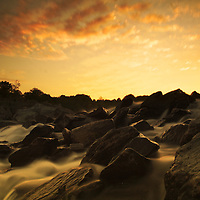 Flowing water in a river with large boulders at sunset
