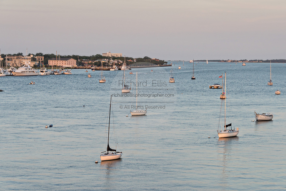 Sailboats moored along the Ashley River with the city skyline at sunset in Charleston, South Carolina.