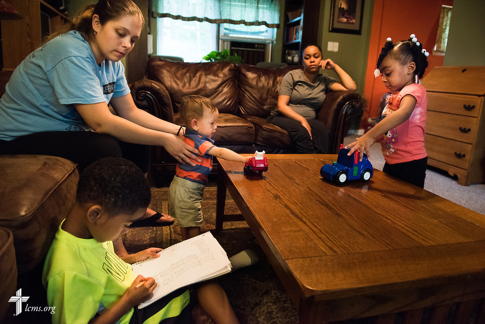 Tiffany Busse (far left) plays with her child Ezekiel Vela while watching Geshawn Harrell work in his notebook, while his sister Jada Harrell plays and their mother Nyia Harrell watches during an evening of playtime at A Place of Refuge on Tuesday, Sept. 1, 2015, in Milwaukee, Wis. LCMS Communications/Erik M. Lunsford