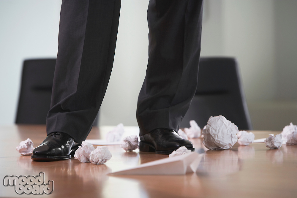 Businessman standing on conference table with crumpled paper low section