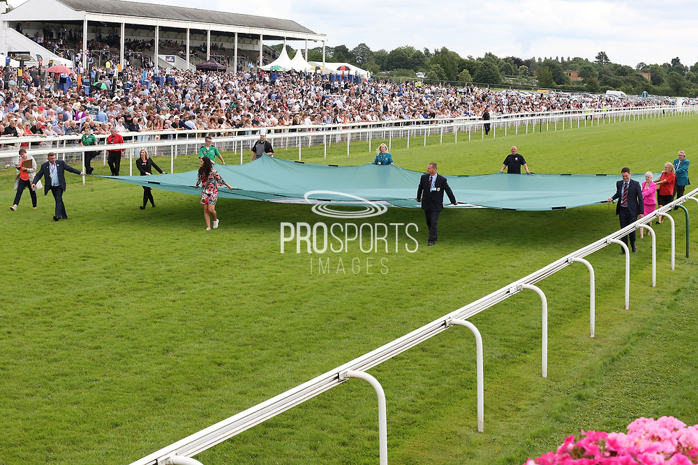 A Special Flag to commemorate the Diamond Anniversary of the John Smiths Cup is paraded down the home straight by various York Racecourse representatives and employees prior to The John Smiths Diamond Jubilee Cup over 1m 2f (£200,000)  during the John Smiths Diamond Cup Meeting at York Racecourse, York, United Kingdom on 13 July 2019.