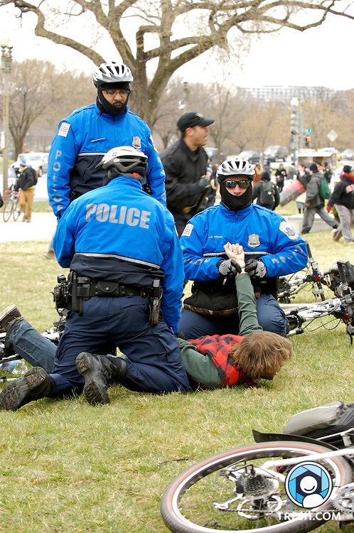 A protester is handcuffed on Constitution Avenue by Washington D.C. Metropolitan Police after a chase on bycicle and foot. Protesters allegedly threw objects at U.S. Park Police.