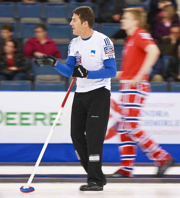 French skip Thomas Dufour, discusses strategy with his teammates as he slides down the ice during France's tie breaker against Norway at the Ford World Men's Curling Championships in Regina, Saskatchewan, April 8, 2011. Norway defeated France 5-4 in 11 ends to advance.<br /> AFP PHOTO/Geoff Robins