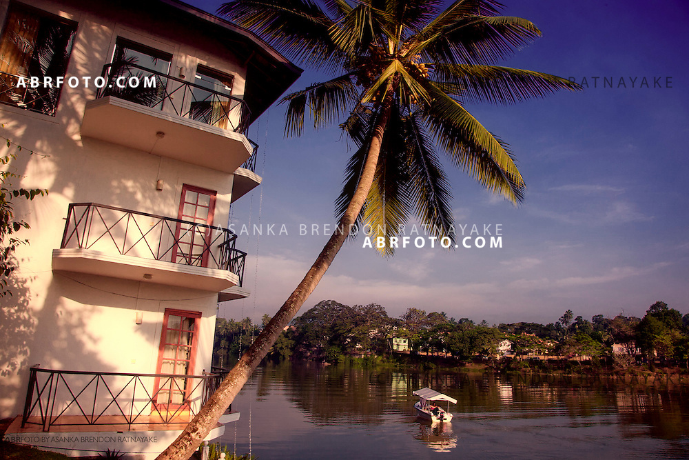 Boat travels along the Mahaweli river pas the Mahaweli reach hotel.