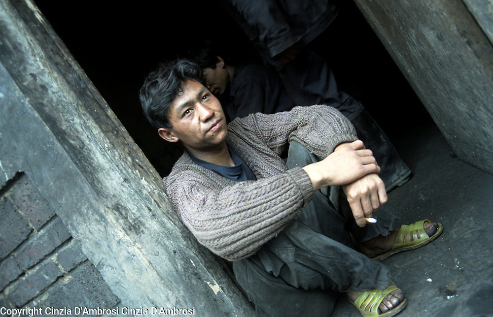 Wu Ci Re, coal miner sitting on the doorstep of a wooden room that he shares with a group of coal miners.  The room is the only space they have to live in and it is situated outside the mine.  Yushe Coal Mine, illegal coal mine on the Laoying Mountain.