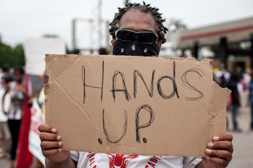 """Hands up"" became the most common phrase one would here walking the streets of Ferguson. A protestor stands with a sign on West Florissant Ave."