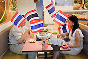 Apr. 19 2010 - BANGKOK, THAILAND: People eat lunch at a restaurant in the Silom area. Workers in the area carried Thai flags and greeted soldiers as heros Monday. Hundreds of Thai soldiers, including reservists and front line units, and riot police moved into the Silom financial district Monday, not far from the red-shirts' main protest rally site, in Ratchaprasong. The heavy show of force is to prevent the Red Shirts from entering the Silom area. Many of soldiers were greeted as heros by workers in the area, who oppose the Red Shirts.   Photo by Jack Kurtz