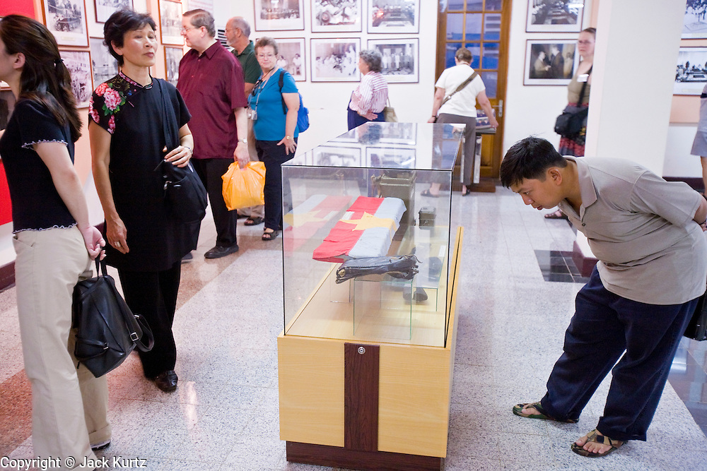 09 MARCH 2006 - HO CHI MINH CITY, VIETNAM: Tourists look at a Viet Cong flag in a museum in Reunification Hall in Ho Chi Minh City. Reunification Hall is the former Presidential Palace used South Vietnamese President Theu during the Vietnam War in Saigon. The complex, which was the heart of the South Vietnamese government, is now called Reunification Hall and is preserved as a museum in the center of Ho Chi Minh City. Photo by Jack Kurtz