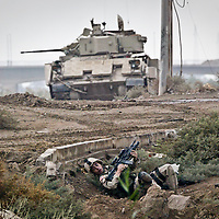 A US soldier takes cover in a ditch as a Bradley fighting vehicle patrols nearby while US troops received heavy fire in Falluja, Iraq. The soldiers battlled insurgent positions on the other side of the river continously for several hours. November 2004.
