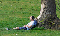 ©Licensed to London News Pictures 08/04/2020  <br /> Greenwich, UK. A man relaxing in the sun while listening to headphones. People get out of the house from Coronavirus lockdown to exercise and enjoy the sunny weather in Greenwich park,Greenwich, London. Photo credit:Grant Falvey/LNP