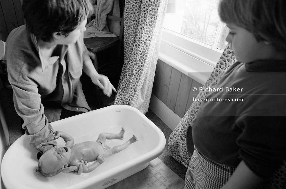 "A two and half year-old girl watches her mother bath her baby brother in the bathroom of her South London home. She looks down at the correct technique that her mum uses by supporting his head with a hand, ensuring the child does not slip further into the warm bath water, the way that many babies drown in even shallow water. Such maternal instincts is how even young children learn to mother and care for their own children in later life, From a personal documentary project entitled ""Next of Kin"" about the photographer's two children's early years spent in parallel universes. Model released."