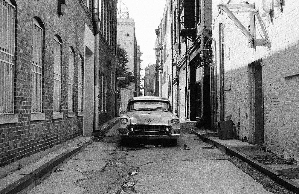 A vintage car stands in a deserted alleyway in the city center of Memphis, USA, 2004