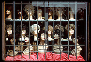 Black and white mannequins display variety of wigs in barred shop window; downtown St. Louis. Missouri