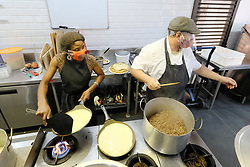 JOHANNESBURG SOUTH AFRICA - MAY 01 Delta Cafe staff preparing food for ready made meals and delivery on May 01, 2020 in Johannesburg South Africa. South Africa moved down to Level 4 of the national lockdown with relaxed restrictions as part of a risk adjusted 5 stage phasing of lockdown measures. This includes allowing of certain restaurants to reopen for trade and prepare hot food as delivered takeaway only. (Photo by Gallo Images/ Dino Lloyd)