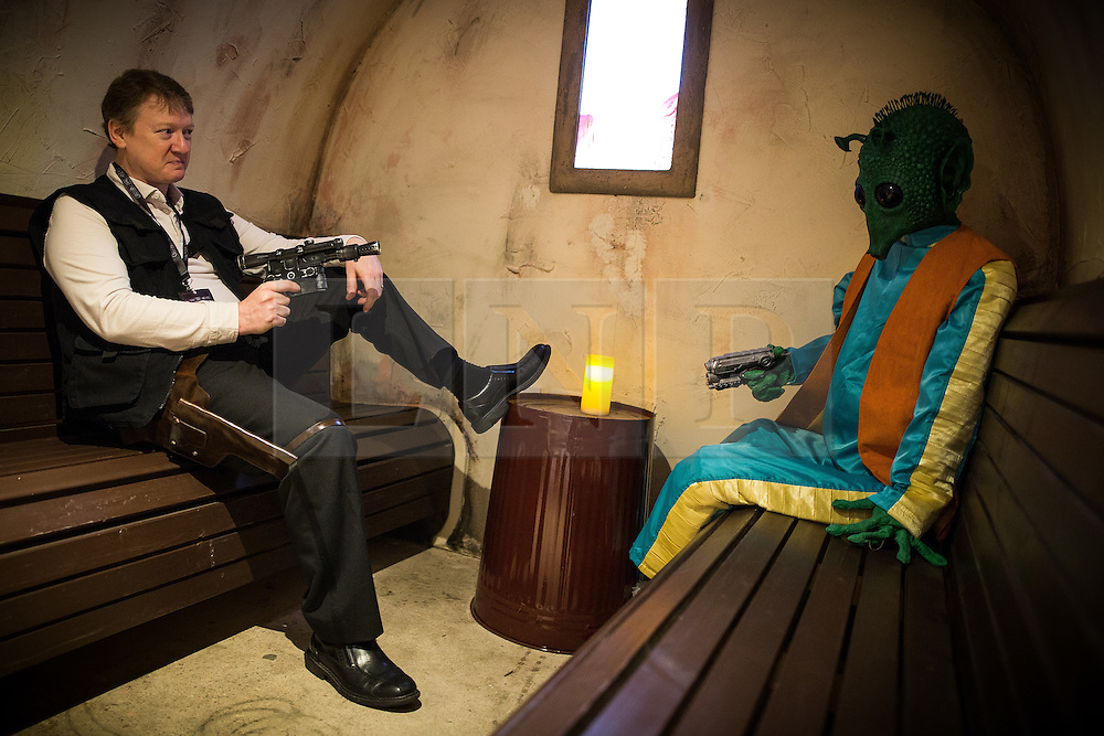 """© Licensed to London News Pictures . 06/12/2015 . Manchester , UK . Han Solo ( Mark Robinson , 48 from Urmston ) about to shoot Greedo FIRST in a bar built as a recreation of the Mos Eisley cantina . I don't like him either . Fans attend Star Wars exhibition """" For the Love of the Force """" at Bowlers Exhibition Centre in Manchester . Photo credit : Joel Goodman/LNP"""