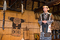 An Ainu man in traditonal clothing gives a performance in a thatched hut.