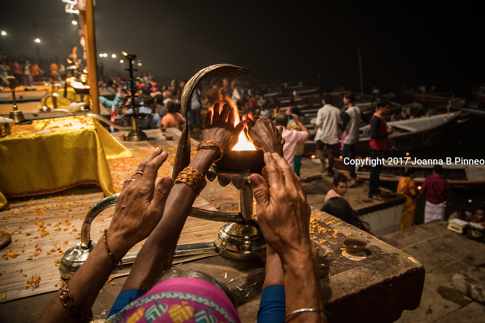 "Dasaswamedh Ghat, Varanasi. After the sacred Aarti ritual is performed each evening at the Dasaswamedh Ghat devotees cup their hands over the flames and to receive the blessing of the river goddess. The word 'aarti' means something that removes the darkness and is often called the ""ceremony of light"".  As one of the most sacred cities in India many people come to the banks of the Ganges River in Varanasi to pray, bathe and participate in sacred purification ceremonies. Between industrial waste, sewage from town and cremation rites the Ganges is a polluted mess."