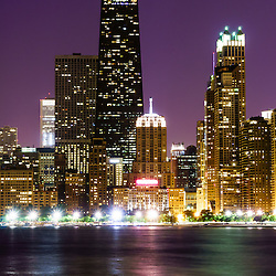 Photo of Chicago night skyline with the John Hancock Center building and other popular downtown Chicago skyline city buildings. The John Hancock Center is one of the world's tallest skyscrapers and is a famous fixture in the Chicago skyline. Photo is vertical and high resolution.