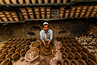 A Uyghur potter in his workshop throws a pot on the potter's wheel in the Old City of Kashgar, along the Silk Road, Xinjiang Uyghur Autonomous Region of far western China. Uyghur people are a Central Asian people of Muslim Turkic origin.