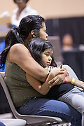 A mother and daughter wait during a free medical mission held by the SC Dental Association on August 23, 2013 in North Charleston, South Carolina. More than 1,000 people showed up to receive free dental and medical care.