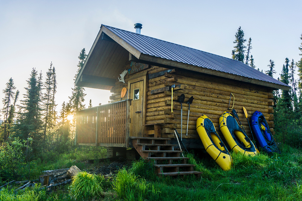 Borealis-LeFevre Cabin, alongside Beaver Creek, is on one of the longest roadless sections of a designated Wild and Scenic River in North America. Fortunately, packrafts make it possible to hike to the road. The sun is setting in the north at 11pm in June in interior Alaska.