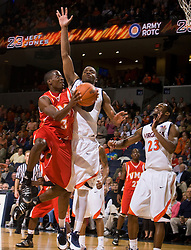 Virginia Military guard Chavis Holmes (3) shoots past Virginia forward Jamil Tucker (12).  The Virginia Cavaliers defeated the Virginia Military Institute Keydets 107-97 in NCAA Basketball at the John Paul Jones Arena on the Grounds of the University of Virginia in Charlottesville, VA on November 16, 2008.