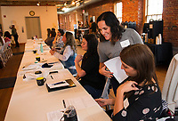 Mia Whalley hands out business strategy worksheets to participants of the CEO Live workshop at Belknap Mill on Friday morning.   (Karen Bobotas/for the Laconia Daily Sun)