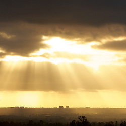 Light rays breaking through the clouds onto the City of Irvine below.