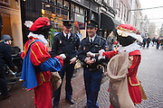 Zwarte Pieten delen strooigoed uit aan twee politieagenten in Utrecht.<br /> <br /> Zwarte Pieten are giving candies to the police in Utrecht