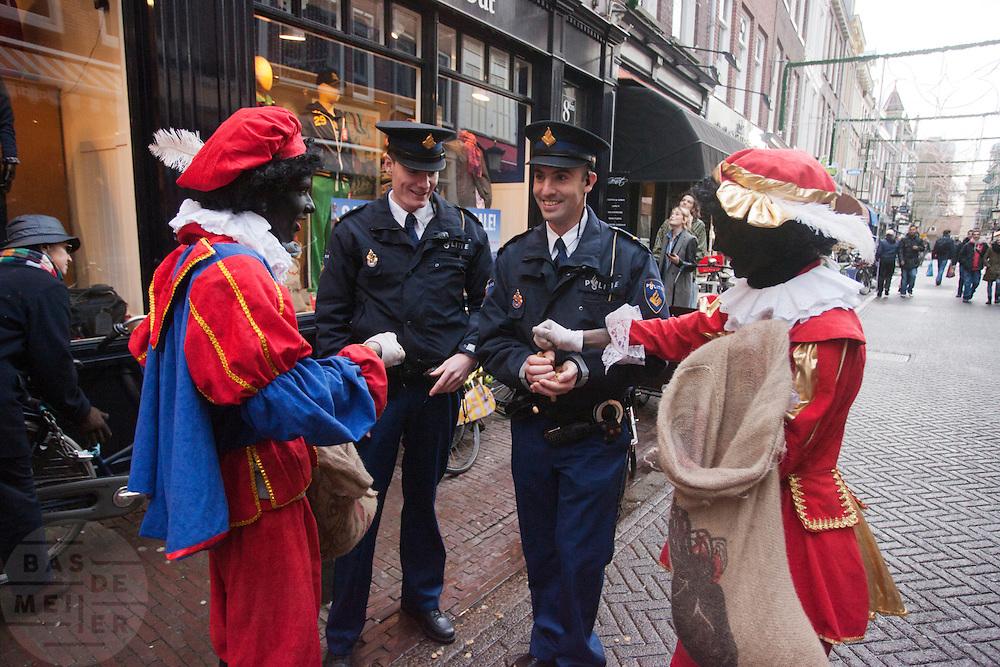Zwarte Pieten delen strooigoed uit aan twee politieagenten in Utrecht.<br /> <br /> Zwarte Pieten are giving candies to the police in Utrecht