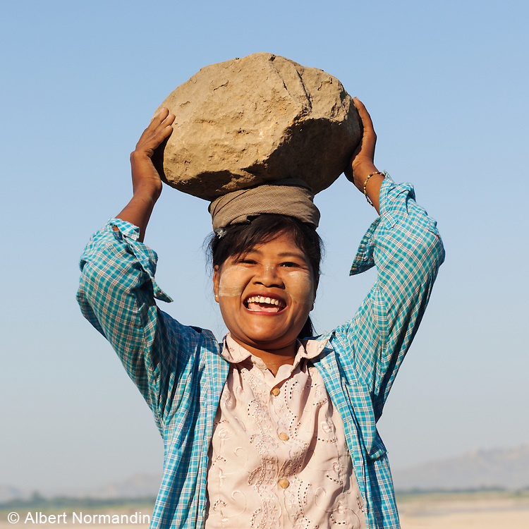 Woman carries and balances rocks on her head for a small salary. Laughing 1 big rock.