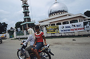 Batak Muslim and Christian girls on motorbike, one in traditional dress and the other in modern western dress, pass by mosque...Batak Indigenous Christian people living on Samosir Island and nearby Lake Toba in Indonesia. There are some 6 million Christian Batak in Indonesia, the world's largest Muslim country of 237 million people, which has more Muslims than any other in the world. Though it has a long history of religious tolerance, a small extremist fringe of Muslims have been more vocal and violent towards Christians in recent years. ..Batak religion is found among the Batak societies around Lake Toba in north Sumatra. It is ethnically diverse, syncretic, liable to change, and linked with village organisations and the monotheistic Indonesian culture. Toba Batak houses are boat-shaped with intricately carved gables and upsweeping roof ridges, and Karo Batak houses rise up in tiers. Both are built on piles and are derived from an ancient Dong-Son model. The gable ends of traditional houses, Rumah Bolon or Jabu, are richly decorated with the cosmic serpent Naga Padoha carved in wood or in mosaic, lizards, double spirals, female breasts, and the head of the singa, a monster with protruding eyes that is part human, part water buffalo, and part crocodile or lizard. The layout of the village symbolises the Batak cosmos. They cultivate irrigated rice and vegetables. Irrigated rice cultivation can support a large population, and the Toba and the Karo live in densely clustered villages, which are limited to around ten homes to save farming land. The kinship system is based on marriage alliances linking lineages of patrilineal clans called marga. In the 1820's Islam came to the southern Angkola and Mandailing homelands, and in the 1850's and 1860's Christianity arrived in the Angkola and Toba region with Dutch missionaries and the German Rheinische Mission Gesellschaft. The first German missionary caused the Dutch to stop Batak communal sacrificial rituals and music, whic