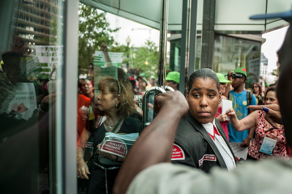 """A security guard looks on as she guards the door at an office building that activists stopped at as they marched through the streets of Washington, D.C. to illuminate the social and economic costs of putting profit in front of the resources, rights and policies that can end HIV/AIDS. The march ended at the White House to demand """"the political will necessary to ensure economic justice for all and to defend and protect the human rights of our marginalized communities, including people living with HIV & AIDS.? The march was part of the 2012 International AIDS Conference in Washington, D.C."""