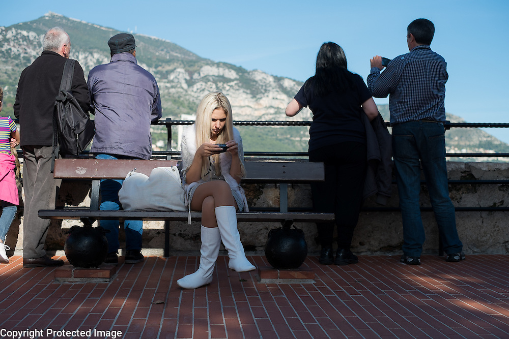 A women looks through travel photos while on a tour overlooking Fontvieille Harbor in Monaco.