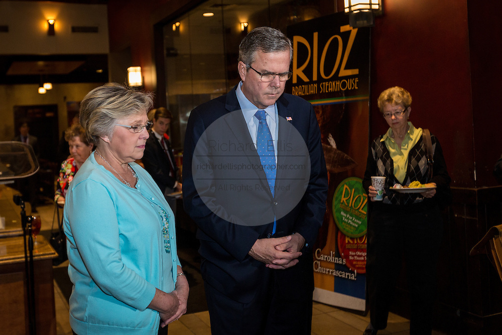 Former Florida Governor and potential Republican presidential candidate Jeb Bush bows his head for a prayer at an early morning GOP breakfast event March 18, 2015 in Myrtle Beach, South Carolina.