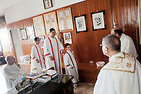 "PERDASDEFOGU, SARDINIA, ITALY - 30 JUNE 2013: Altar boys prepare and priests prepare for the mass celebrating Claudina Melis' 100th birthday in St. Peter's church in Perdasdefogu, Italy, on June 30th 2013.<br /> <br /> Last year, the Melis family entered the Guinness Book of World Records for having the highest combined age of any nine living siblings on earth — today more than 825 years. The youngest sibling, Mafalda – the ""little one"" – is 79 years old.<br /> <br /> The Melis siblings were all born in Perdasdefogu to Francesco Melis and Eleonora Mameli, who had a general store. Consolata, 106, is the oldest, then Claudia, 100; Maria, 98; Antonino, 94; Concetta, 92; Adolfo, 90; Vitalio, 87; Fida Vitalia, 81; and Mafalda, the baby at 79. Their descendants now account for about a third of the village."