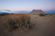 Sunrise and moonset at Factory Butte in the southwestern desert of Utah