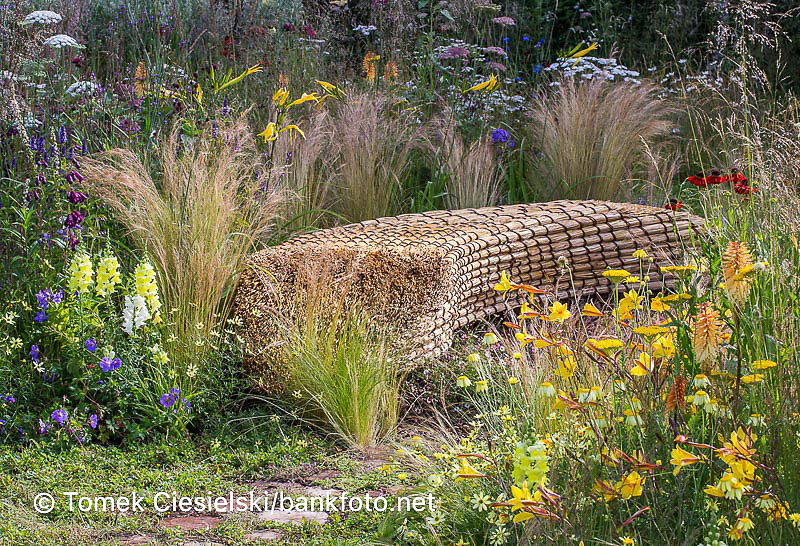 Strawy bench surrounded by summer perennials and ornamental grasses