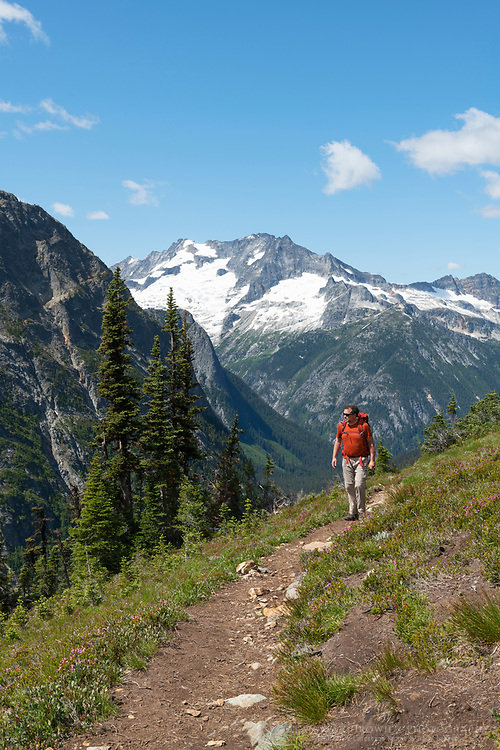 Adult male hiker with red backpack on Fisher Creek Trail near Easy Pass. Mount Logan is in the distance. North Cascades National Park Washington