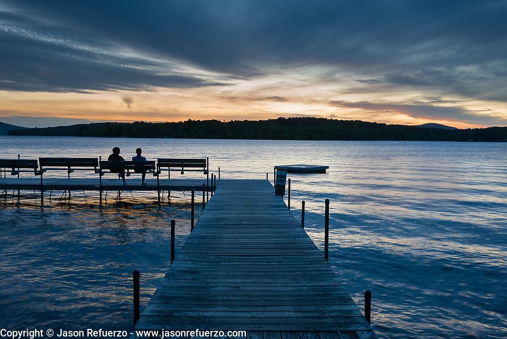 Two friends watching the sunset along Rangley Lake